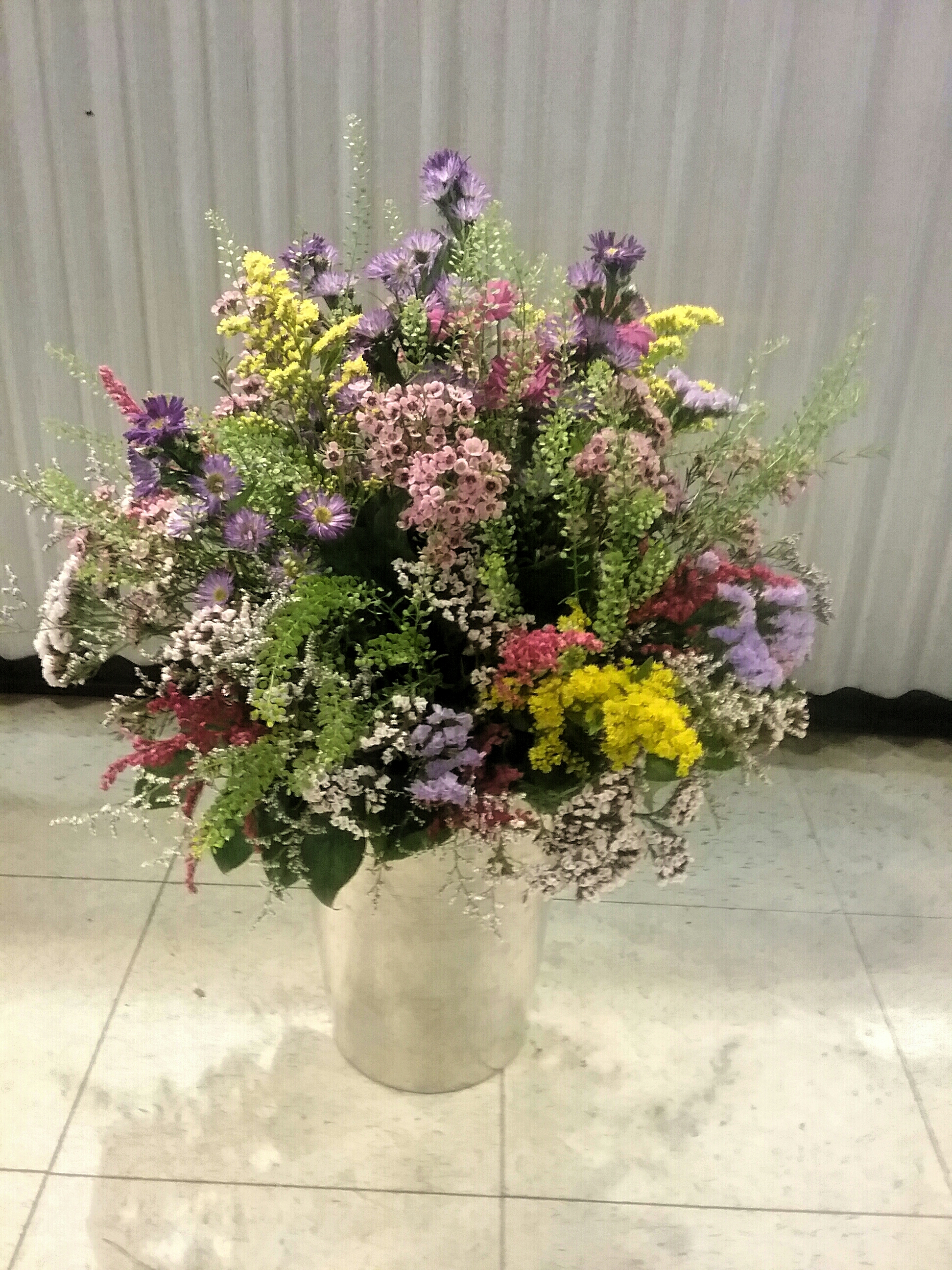 Wild flowers bouquet in a pot of metal